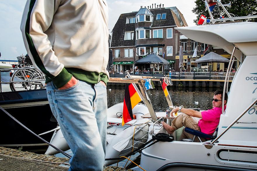 Nederland, Lemmer, 7 sept 2014<br /> Bootjesvolk aan de kade in Lemmer. In Lemmer komen in het seizoen dagelijks veel mensen met een boot aanleggen om er de nacht door te brengen.<br />  <br /> Foto: (c) Michiel Wijnbergh
