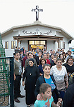 People leave a Catholic Church after Mass in a displaced persons camp in Ankawa, near Erbil, Iraq, on April 11, 2016. Residents of the camp are mostly Christians displaced by ISIS in 2014.