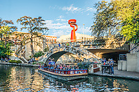 This is another image of the San Antonio river walk with the Tourch of Freedom on the street above. The river walk draws tourist from all over for it restaurants and hotel located along the water.  Tour boats are seen at all times as they take people on a tour of the city by water.