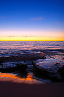 Sunset at Grant street North Cottesloe with the rocks exposed by the receding wave and the sunset reflected in the sand..
