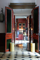 At the end of an enfilade the living room is lit with a group of old-fashonied tapers