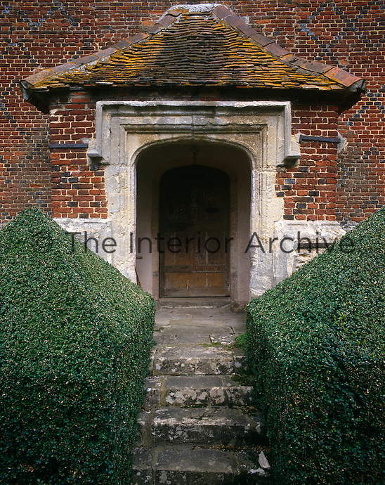 The approach to the main entrance door to Beckley Park between topiary hedges