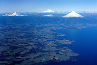 Aerial of lake district (Los Lagos region) with snow-covered volcanoes, southern Chile (north of Puerto Montt): Lake Llanquihue; Center, distant: Cerro Tronador, extinct volcano (3491 m); Right: Osorno volcano (2652 m); Left: Puntiagudo volcano (2493 m)