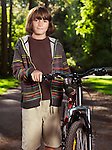 Portrait of a child, ten year old boy, with a bicycle in a park.