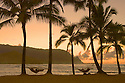 "Couple in hammocks on beach at sunset, Hanalei Bay and view to ""Bali Hai""; Princeville Resort, Kauai, Hawaii."