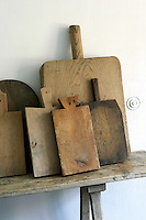 A functional still-life of a collection of antique chopping boards on a shelf in the kitchen