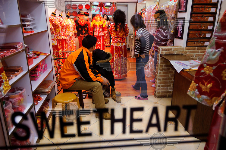 A couple in a shop called 'Sweetheart' in the city's wedding dress market in the south of the city, feeding a new trend of brides who are buying their dresses rather than hiring them, in this case a Chinese style one.