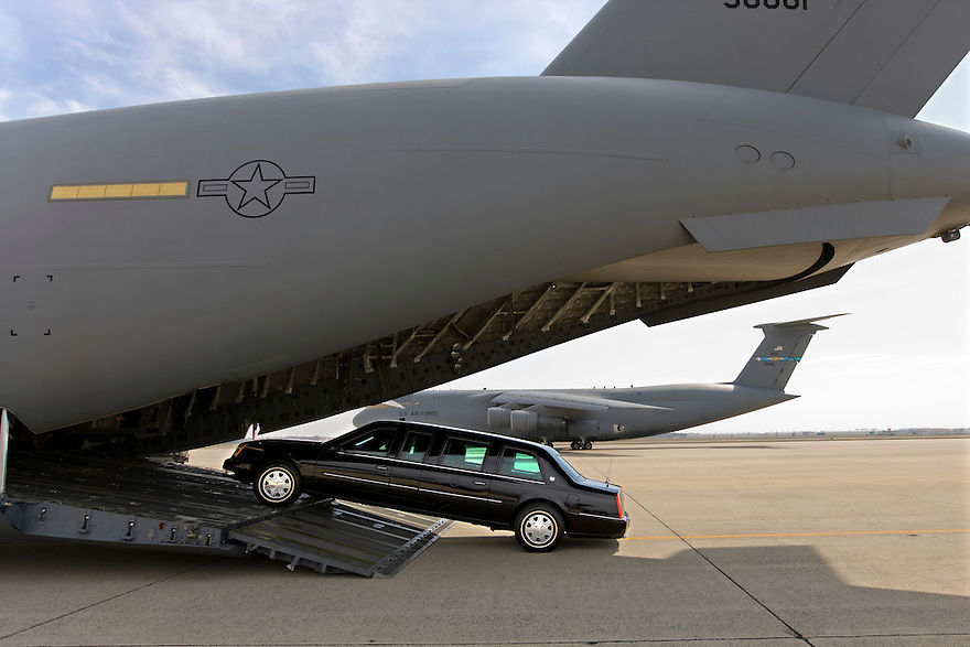 """A Presidential limousine is loaded onto a C5 military transport plane bound for eastern Europe, where President Bush is headed next week.  A """"secure package"""" of motorcade vehicles, including the limousines and a fleet of Secret Service SUVs is transported to the site of every presidential visit. ..Photo by Brooks Kraft/Corbis........."""