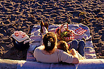 Mother and daughter having a picnic at the beach with snacks watching sunset Edmonds, Washington State USA.