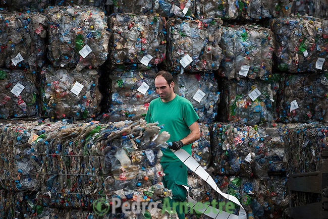 "An employee works near stacks of plastic waste collected in the sea by fishermen at a plastic processing plant in Chiva, near Valencia on November 3, 2015. Ecoalf, a Spanish Madrid-based firm founded in 2010, has already launched ""a new generation"" of clothes and accessories made from plastic bottles, old fishing nets and used tires found on land. © Pedro ARMESTRE"