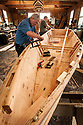 Bob Deming (blue shirt), and Andrew Linn (green shirt), building a wooden boat at the Port of Toledo Community Boathouse; Toledo, Oregon.