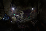 Miners inside a mine in Potosi, Bolivia, chew coca leaves. The mine produces silver and other metals.