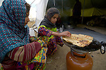 Following an October 8, 2005, earthquake, two girls cook in a tent city outside Balakot, Pakistan. The quake measured 7.6 on the Richter scale and killed more than 74,000 people in northern Pakistan.