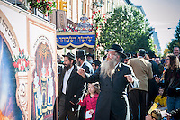 Members and friends of the Chabad of Harlem celebrate the completion of their Sefer Torah with a Torah parade (Hachnasat Sefer Torah) through the streets of Harlem in New York on Sunday, October 27, 2013. The ten year old synagogue commissioned the hand-written parchment scroll (which contains 304,805 Hebrew letters) two years ago. Harlem was once home to over 200 synagogues before the Great Depression and current census records have shown that the caucasian population now outnumbers african-americans.  (© Richard B. Levine)
