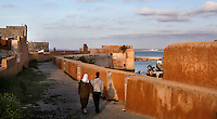 Couple walking on the defensive walls of the Portuguese Fortified city of Mazagan, 16th century, El Jadida, Morocco. El Jadida, previously known as Mazagan (Portuguese: Mazag√£o), was seized in 1502 by the Portuguese, and they controlled this city until 1769. The fortification with its bastions and ramparts is an early example of Renaissance military design. Picture by Manuel Cohen