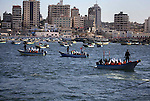 Palestinian children sit on boats before launching in water model boats, with their names and countries' names on sails, during a rally to protest against the Israeli siege of the Gaza Strip on November 30, 2013 at Gaza City harbour. Photo by Ashraf Amra