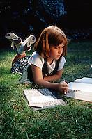 Little girl doing homework outside in the grass.