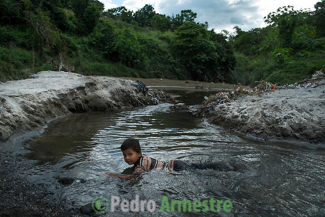 November 07, 2014. &quot;Water it&acute;s the real thing&quot;<br /> Anderson Salguero swims in a river contaminated called Acelhuate (Nejapa, El Salvador). Anderson and his family have to walk near two hours to get the river because they don&acute;t have water at home.<br /> The people of Nejapa in El Salvador, have no drinking water because the Coca -Cola company overexploited the aquifer in the area, the most important source of water in this Central American country. This means that the population has to walk for hours to get water from wells and rivers. The problem is that these rivers and wells are contaminated by discharges that makes Coca- Cola and other factories that are installed in the area. The problem can increase: Coca Cola company has expansion plans, something that communities and NGOs want to stop. To make a liter of Coca Cola are needed 2,4 liters of water. &copy;Calamar2/ Pedro ARMESTRE