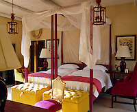 In one of the bedrooms of a country house hotel in Africa a fresh colour scheme of cream with yellow and pink accents creates a warm and sunny feel