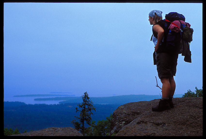 A BACKPACKER LOOKS OUT FROM MOUNT FRANKLIN WHILE HIKING ALONG THE GREENSTONE TRAIL ON ISLE ROYALE NATIONAL PARK.