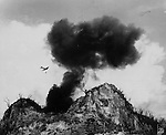 Swooping lower that the huge column of smoke rising from a preceding bomb, an American Corsair fighter plane releases its bomb on a Japanese posiiton in the hills of Peleliu. The assault was delivered against remnants of the enemy who were hiding in the caves from which it was a difficult task for the Marine foot soldiers to blast them.