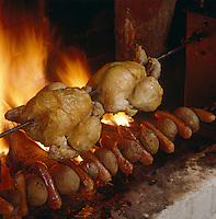 Organic chickens spit-roasting over an open fire in the kitchen