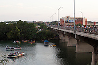 Bat cruise boats, kayaks and canoes gather on Town Lake while crowds gather on the Congress Avenue to watch the Bats nightly flight spectacle