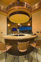 Rounded wet bar is seen under under round ceiling with copper facia