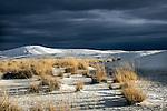 Barren desert scene ith white sand under a stormy sky