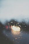 car headlights blurred through a rain covered window on a road in England