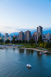 The view of Downtown Vancouver and the mountains in the distance from the Burrard Street Bridge at dusk.