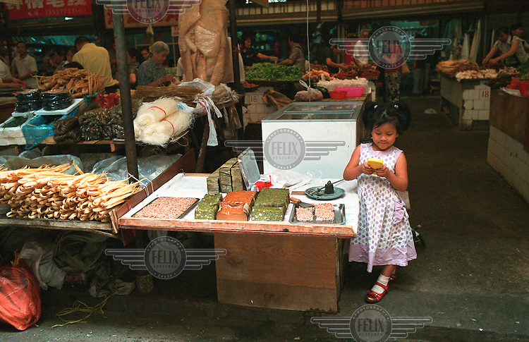 A young girl watches a vegetable stall while playing a video game in Guilin.