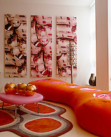 This unusually shaped sofa in the living room is matched by equally colorful art and furnishings