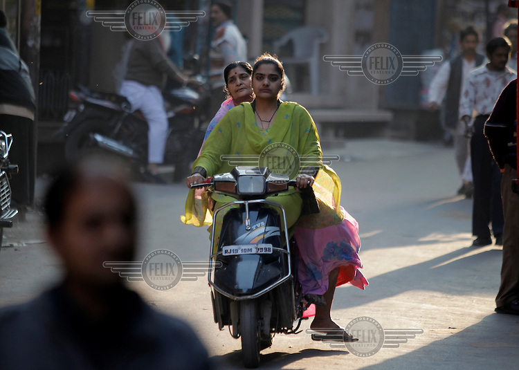 Two women on a motorcycle in the streets in Jodhpur old city. Jodhpur is the second largest city in the Indian state of Rajasthan. Jodhpur is a popular tourist destination, featuring many palaces, forts and temples, set in the stark landscape of the Thar desert..The city is known as the Sun City for the bright, sunny weather it enjoys all year. It is also referred to as the Blue City due to the blue-painted houses around the Mehrangarh Fort.
