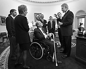 James Brady along with wife Sarah and son Scott meet with United States President Bill Clinton in the Oval Office of the White House in Washington, D.C. moments before dedication of the press office in Brady's honor, February 11, 2000. In the background are John Podesta, Bruce Reed and Joe Lockhart.       .Mandatory Credit: William M. Vasta / White House via CNP