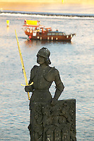Czeck Republic, Prague, statue on Charles Bridge with tour boat in backgound (selective focus)