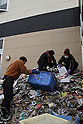 (March 31st, 2011)  Almost three weeks after the tsunami the city of Sendai, with a population of over a million, struggles with the after effects.  Especially hard hit was the low-lying port area of Tagajo.  Outside of Naniwa Books, an internet cafe, workers throw ruined books into a waiting garbage truck..