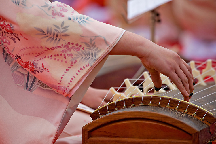 Dressed in a traditional kimono, a young woman plays a 13-stringed koto during the Sakura Matsuri at the Himeji Castle