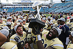 The Georgia Tech Yellow Jackets celebrate after defeating the Kentucky Wildcats 33-18 in the TaxSlayer Bowl at EverBank Field on Saturday, December 31, 2016 in Jacksonville, Florida. Photo by Michael Reaves | Staff.