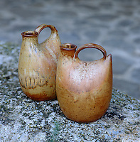 A pair of organically shaped stoneware pots by Ann Milliken on top of a stone wall