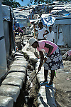 "A woman cleans a drainage canal in the largest ""tent city"" of Haitian earthquake survivors, located on a former nine-hole golf course in Port-au-Prince. The Petionville Club is host to more than 44,000 people."