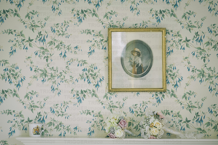 Small framed print on a wall with wedding bouquet of flowers on mantlepiece