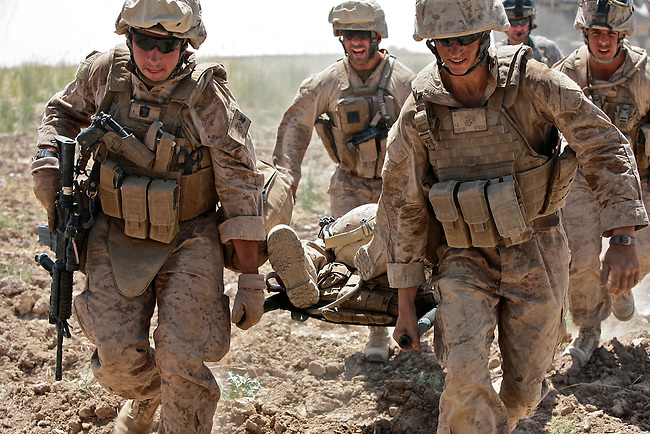 Marines carry a wounded comrade to a waiting medevac helicopter in Helmand province, southern Afghanistan. Medevac crews with Company C, 3rd Battalion, 82nd Combat Aviation Brigade have pulled dozens of injured NATO and Afghan troops off the battlefield since a major offensive in the region began earlier this month. July 16, 2009. DREW BROWN/STARS AND STRIPES