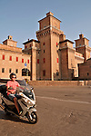 Man on a motorbike rides past the Castle Estense, a medieval castle with a moat around it in the center of town