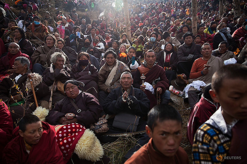 Ethnic Tibetan people pray on the hill above a Buddhist laymen lodge where thousands of monks and nuns gather for morning chanting session during the Utmost Bliss Dharma Assembly, the last of the four Dharma assemblies at Larung Wuming Buddhist Institute in remote Sertar county, Garze Tibetan Autonomous Prefecture, Sichuan province, China October 30, 2015. The eight-day gathering starts every year around the 22rd of the ninth month on Tibetan calendar, the great day of Buddha's Descending from Tushita Heavens. The Larung Wuming Buddhist Institute, located some 3700 to 4000 metres above the sea level was founded in 1980 by Khenpo Jigme Phuntsok, an influential lama of Nyingma sect of Tibetan buddhism with only around 30 students but is now widely known as one of the biggest centres to study Tibetan Buddhism in the world. Picture taken October 30, 2015.  REUTERS/Damir Sagolj