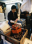 A vendor cleans shellfish for sale at the Tsukiji Fish Market in Tokyo, Japan where a skilled army of licensed middlemen and buyers purchase tuna and a variety of seafood for sale in the market's 1,400 shops. Because of the Japanese passion for freshness, all the fish sold will be consumed by Tokyo residents the following day.  (Jim Bryant Photo).....