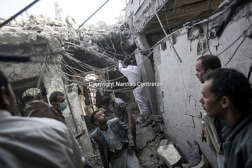 July 02, 2015 - Sana'a, Yemen: Houthi militants look for survivors at the rubble of a house building after it was hit by a fighter jet belonging to the Saudi coalition in the Yemeni capital Sana'a. Two children of the family were buried and died under the rubble during the missile attack while the mother and a two other children were taken to a nearby hospital. The mother and one of the children survived the attack as another one child died by his injuries. (Photo/Narciso Contreras)