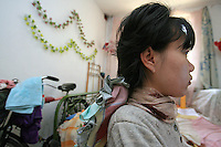 Li Yan sits in front of her computer in her home in Yinchuan, Ningxia Province, China, on May 7, 2007. Li Yan spends up to 10 hours per day in front of her computer, producing colourful paintings and writing her blog. 28-year-old Li Yan suffers from motor neuron disease also known as amyotrophic lateral sclerosis (or ALS), the same illness that has thereotical physicist Stephen Hawking. Li Yan asked China's National People's Congress (NPC) to consider a draft on euthanasia. Photo by Lucas Schifres/Pictobank