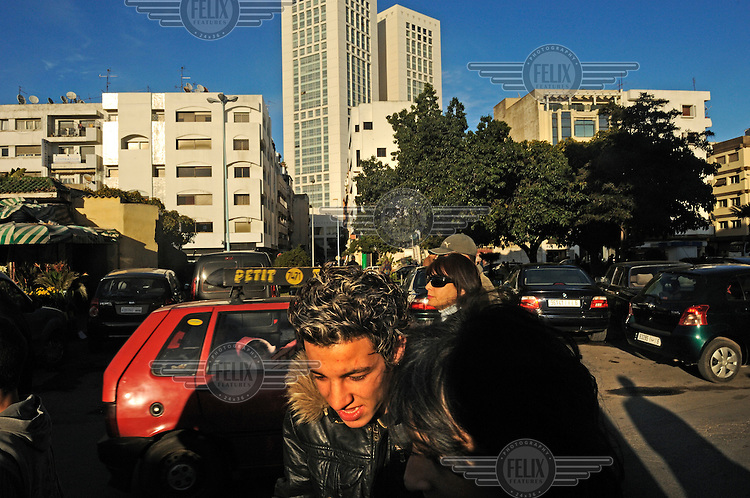 A young man sporting blonde highlights in his hair in the fashionable Maarif district. Beyond him are the towers of the Casablanca Twin Centre.