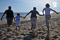 Family holding hands running away on beach (Licence this image exclusively with Getty: http://www.gettyimages.com/detail/83154264 )